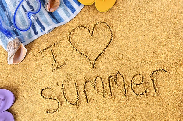 I Love Summer written in sand, with towel, seashells and flip flops