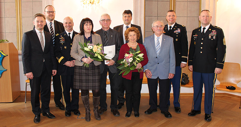 "Walter Brunner, pictured here in front with light gray jacket, was recognized by local and state officials as the ""best ambassadors and promoters of German-American friendship."" Brig. Gen. Christopher G. Cavoli of the 7th Army Joint Multinational Training Command, Col. Mark. A. and Mrs. Colbrook, Command Sgt. Maj. Robert G. and Mrs. Todd of U.S. Army Garrison Bavaria, City of Grafenwoehr Mayor Edgar Knobloch and members of and Bavarian state parliament Petra Dettenhöfer, Annette Karl and Tobias Reiss were among the congratulates."