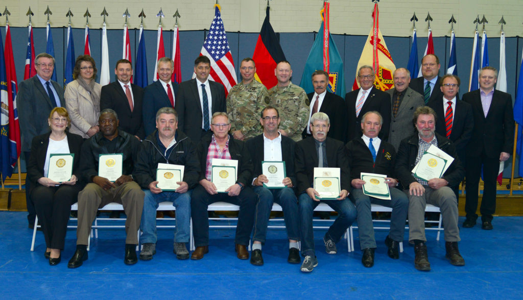 Hannah St. Clair, Sherman Watts, Alfons Lohner, Reinhold Meier, Roland Pueschl, Karl Raps, Wilfried Heitzer and Josef Schecklmann, seated left to right, were recognized for 40 years of service to the U.S. Army at the quarterly civilian awards ceremony held on Tower Barracks April 15. (Photo by Gerhard Seuffert)