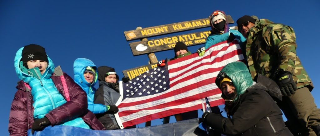 Joann Valenzuela, in the middle in the black cap, holds the flag she carried from Vilseck, Germany to the peak of Mount Kilimanjaro in Tanzania, Africa, on Feb. 14, 2016, along with other members of the Tragedy Assistance Program for Survivors (TAPS) expedition. Written on the flag were the names of 97 Soldiers from Grafenwoehr and Vilseck who were killed in Operation Enduring Freedom and Operation Iraqi Freedom.