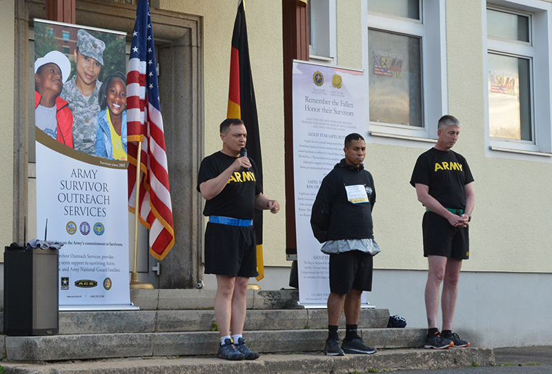 Col. Patrick Ellis (left), commander of 2nd Cavalry Regiment, accompanied by professional boxer Hector Camacho Jr. and Regimental Command Sergeant Major Steven Brown, speaks at the Run to Honor 5K May 24 at Rose Barracks. (Photo by Payton Porter, USAG Bavaria Public Affairs)